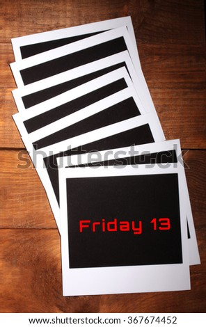 Photo paper with text Friday 13 on wooden background - stock photo