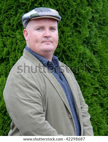 photo portrait of a male outside in jacket and tweed hat - stock photo