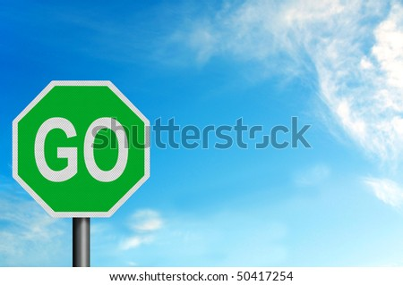 Photo realistic metallic reflective 'Go' sign, against a bright blue sunny summer sky. With space for your text / editorial overlay - stock photo