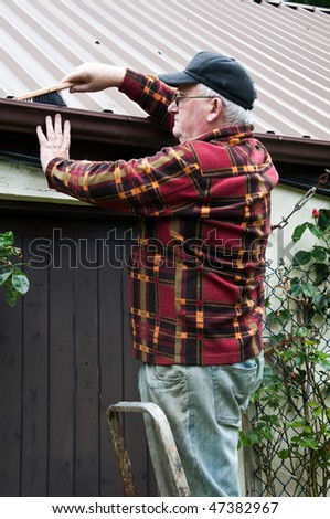 photo senior male glasses working outside doing repairs - stock photo
