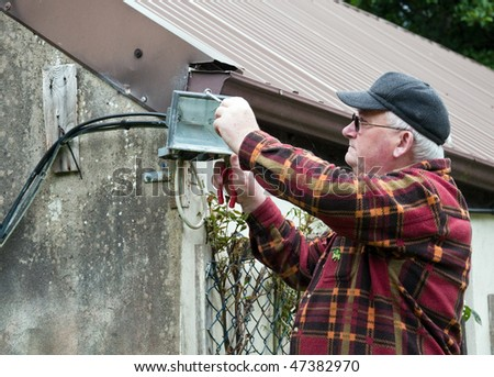 photo senior male glasses working outside doing repairs