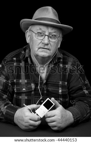 photo senior male listening to mp3 music player - stock photo