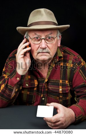 photo senior male with hat on phone with white card - stock photo