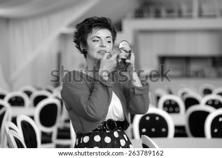 Photo session of an expressive,short haired brunette woman during making up session. Black and white photography