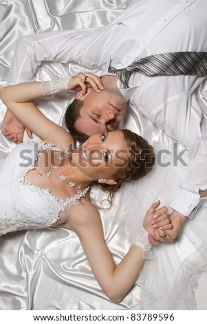 photo shoot of two newlyweds are in bed - stock photo