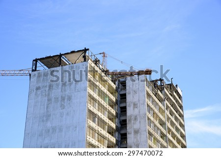 photo showing the demolition of a skyscraper with a high crane - stock photo