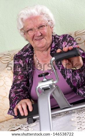 Photo shows a grandma in her flat. Shoe making some sports. Studio Light - stock photo