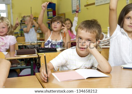 Photo shows a little schoolboy in the classroom. He feels boring during the lesson, not so the other children around him. - stock photo