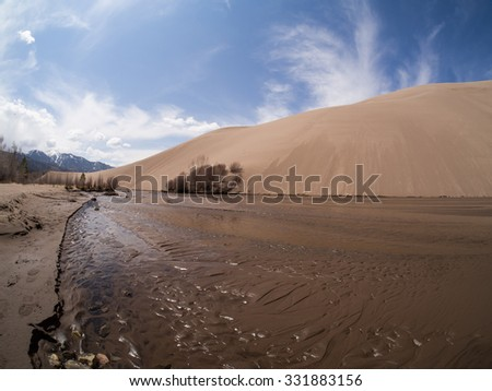 Photo shows close up view of Medano Creek at Great Sand Dunes National Park in Colorado.  Behid the creek is a tall sand dune, with tall snowy mountains behind and blue skies above - stock photo