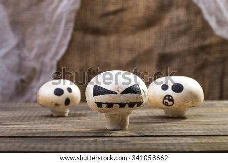 Photo still life set of three Halloween white button mushrooms champignons with ghost face smiles drawn in black felt pen standing on wooden table over blurred rustic background, horizontal picture  - stock photo