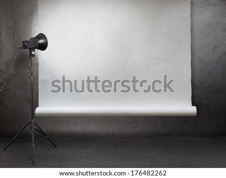 photo studio in old grunge room with concrete wall and paper background  - stock photo