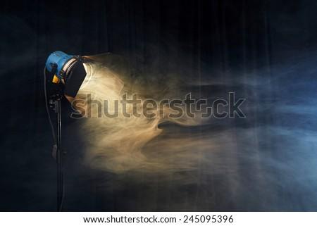 Photo studio lighting equipment on black background with smoke - stock photo
