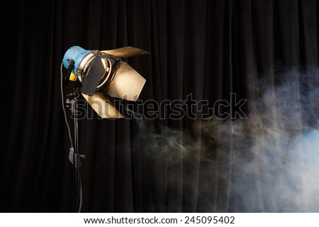 Photo studio lighting equipment on black background with smoke - stock photo
