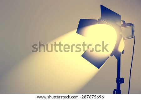 Photo studio with lighting equipment on wall background - stock photo