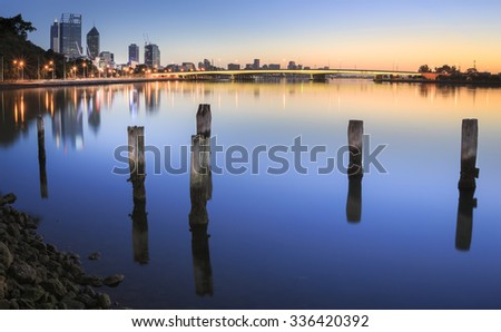 Photo taken from in front of the old swan brewery in Perth Western Australia. Looking back over the City of Perth and the Narrows bridge showing some old landmark timber poles in the Swan River. - stock photo