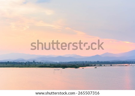 photo view of lake with mountain against sunset sky  - stock photo