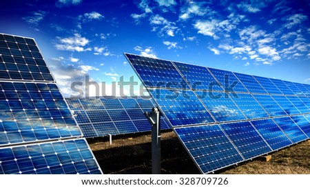Photo voltaic solar panels and blue sky with clouds - stock photo