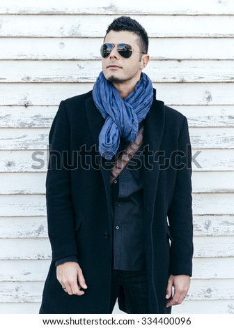 Photo with handsome man in coat on white wooden background,selective focus - stock photo