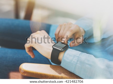 Photo Woman Relaxing Modern Loft Studio.Girl Enjoying Generic Design Smart Watch.Female Hands Touching Screen Smartwatch.Free Time Management. Horizontal. Burred background. Film effects. - stock photo