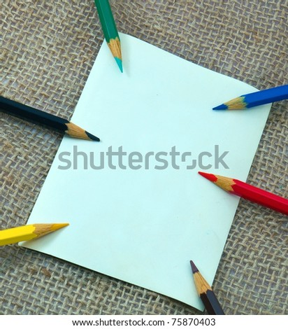 Photocard on sack material with colorful pencils - stock photo