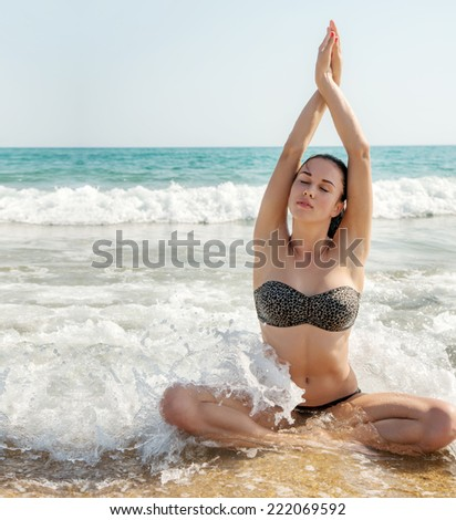 Photograph of a beautiful woman relaxing and meditating on a beach in the waves of the sea. Yoga poses. Enjoy life.  Room for text. - stock photo