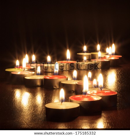 photograph of a black background with candles to give a warm and romantic atmosphere - stock photo
