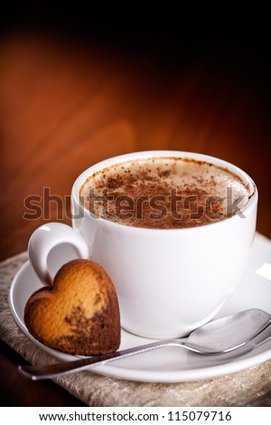 Photograph of a hot cup of coffee with a heart shaped biscuit