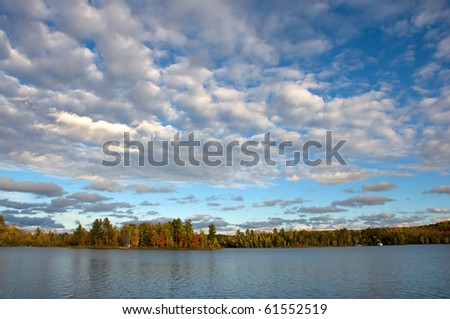 Photograph of a lake in the Upper Peninsula of Michigan in early evening, shot in the midst of Autumn with beautiful fall colors and spectacular sky.  Truly a beautiful photograph.
