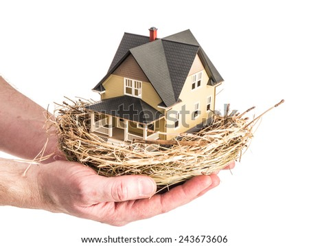 Photograph of a man holding a bird's nest with a miniature home in the nest, illustrating the concept of real estate investment as part of a retirement plan. - stock photo