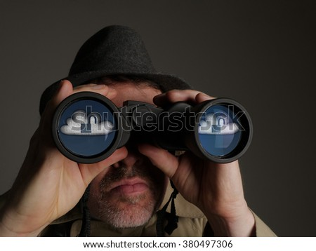 Photograph of a man in trench coat and hat looking through binoculars with reflected symbols in the lenses.