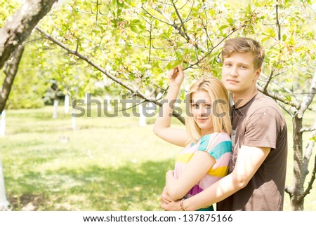 Photograph of a perfect couple holding and hugging each other while posing for the camera on a picnic date. - stock photo
