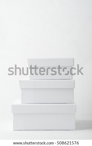Photograph of a stack of three plain white gift or storage  boxes, closed with lids.