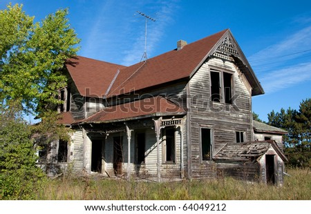 Photograph of an old abandoned and spooky home in the central part of Wisconsin with a beautiful blue sky in the background, and surrounded by the colors of late summer and early autumn. - stock photo