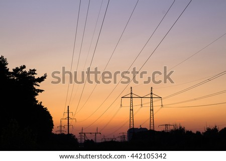 photograph of high-voltage towers at sunset