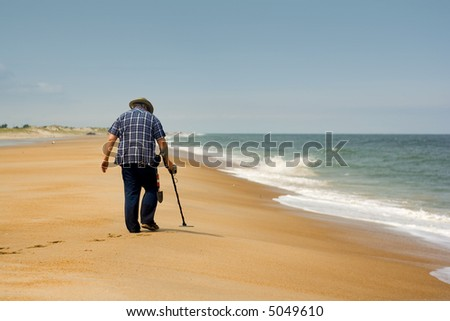 Photograph of man using a metal detector to search for lost treasure on a beach. - stock photo