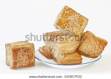 Photograph of square puff croissant pastry Zu-Zu in white porcelain plate. The main subject is isolated on white background, and supported with corresponding clipping path.