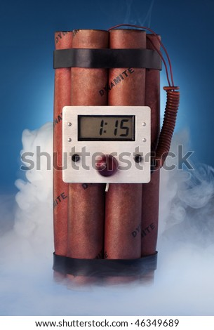 Photograph of stick of dynamite with a timer, smoke on a blue background - stock photo