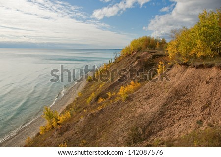 Photograph of the high bank of an eroded Lake Michigan shoreline with exposed dirt and vegetation trying to establish a foothold. - stock photo