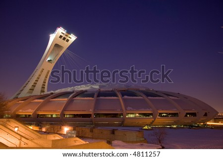 Photograph of the Montreal Olympic Stadium under a gorgeous violet sky. Check out images from the same angle taken during a storm or during a sunny day. - stock photo