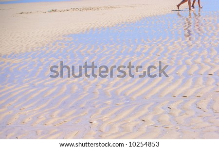 Photograph taken at Henley Beach featuring textured corrugations in the sand at low tide with the legs and reflection of a father and son walking ashore (Adelaide, South Australia). - stock photo
