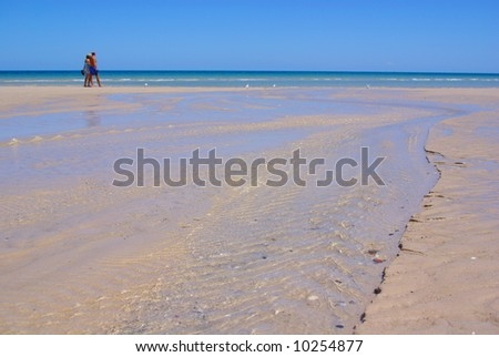 Photograph taken at Henley Beach featuring the small trickle at the mouth of the River Torrens, with a couple walking alongside (Adelaide, South Australia). - stock photo