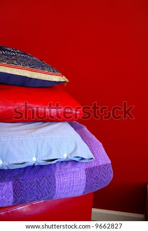 Photograph taken featuring stacked cushions and pillows in front of a red feature wall in a suburban home (Adelaide, South Australia). - stock photo
