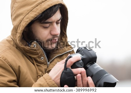 Photographer adjusts the camera at river
