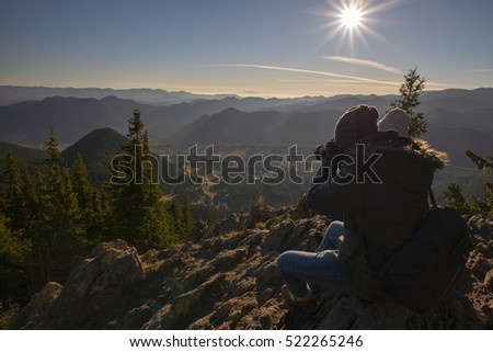 Photographer and girlfriend on top of mountain taking pictures
