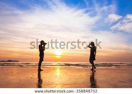 photographer and model, beach photo shooting at sunset, man taking pictures of woman