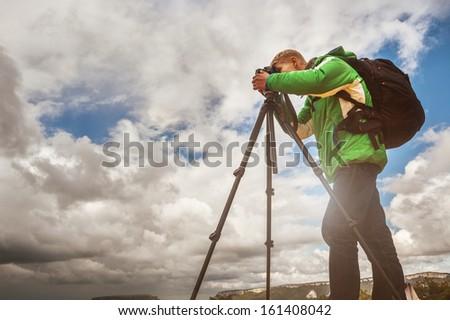 Photographer at work in mountain terrain - stock photo