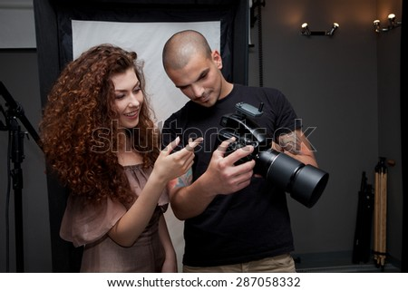 Photographer at work with model in the professional studio - stock photo