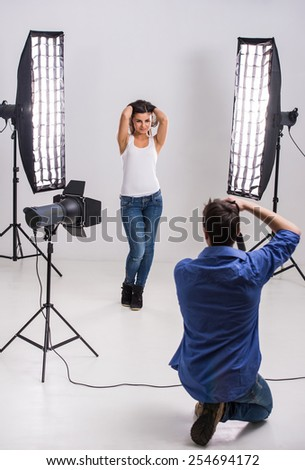 Photographer at work with model in the professionally equipped studio. - stock photo
