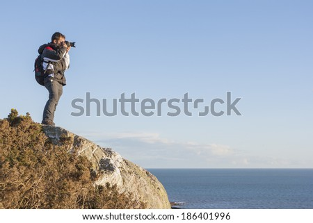 Photographer backpacker at the cliff - stock photo