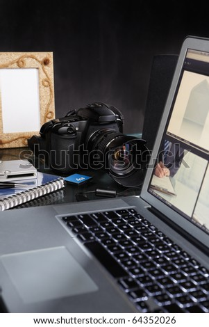 Photographer desk with laptop, DSLR camera and all other stuffs around - stock photo